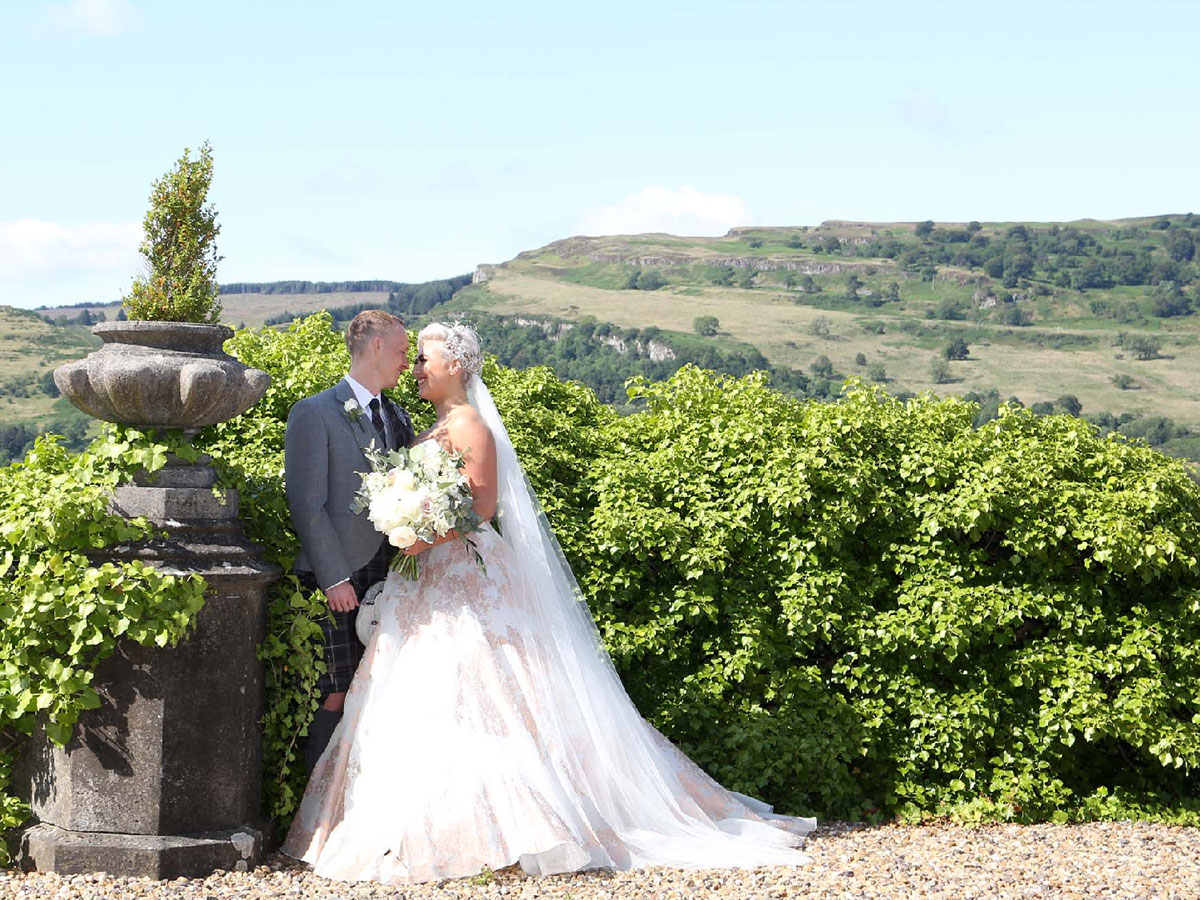 bride-and-groom-against-backdrop-of-hills