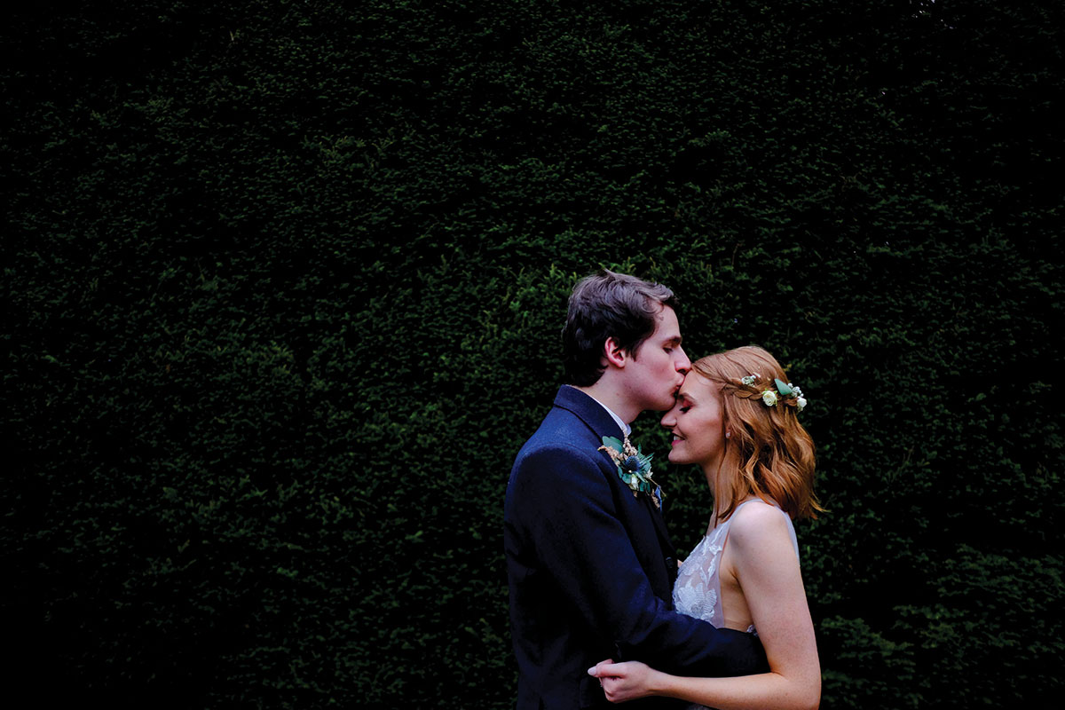 groom-kissing-brides-head-in-front-of-big-hedge