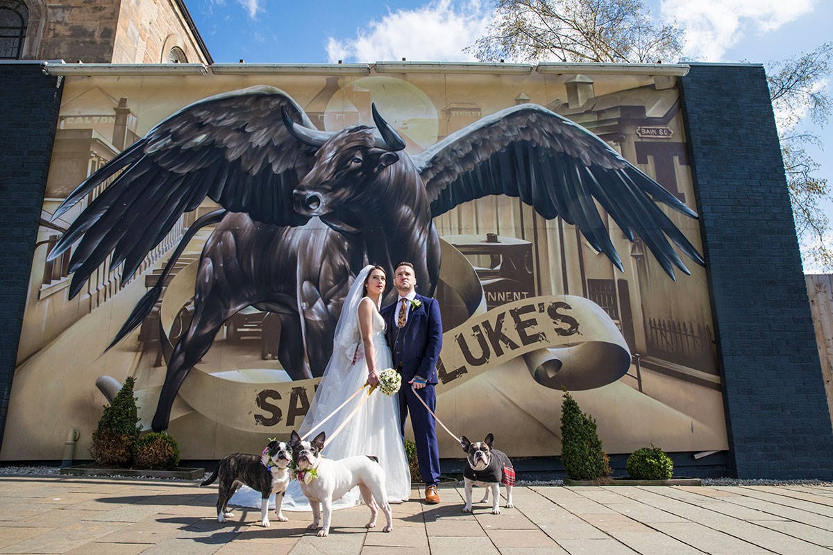 bride-and-groom-outside-saint-lukes-with-three-dogs