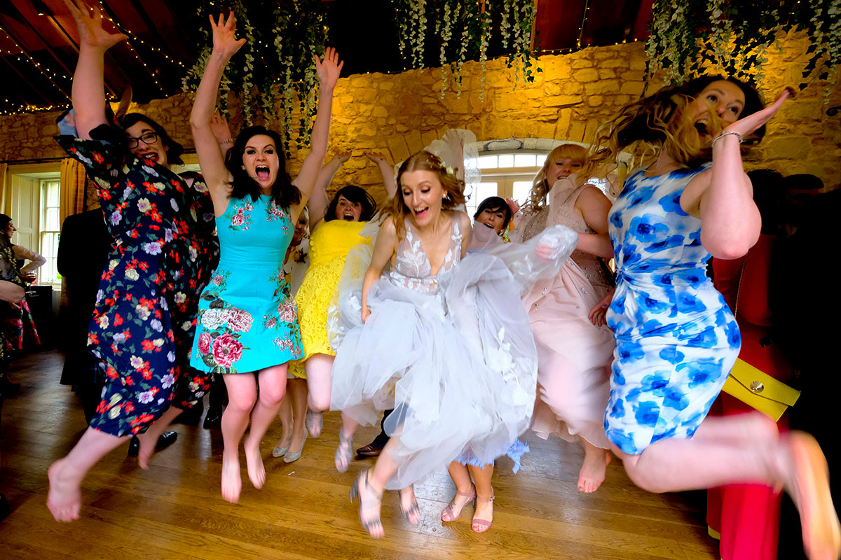 bride-and-friends-jumping-on-dancefloor