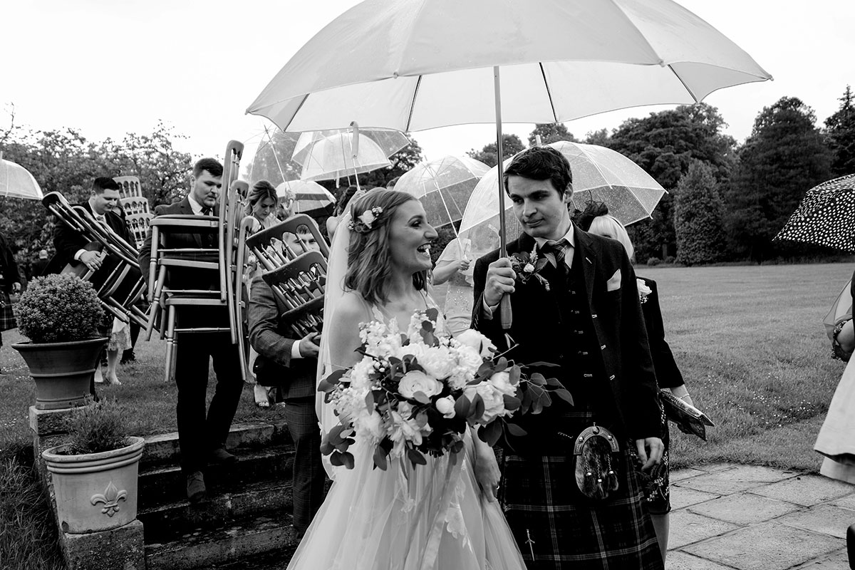 groom-covering-bride-with-umbrella-after-outdoor-ceremony