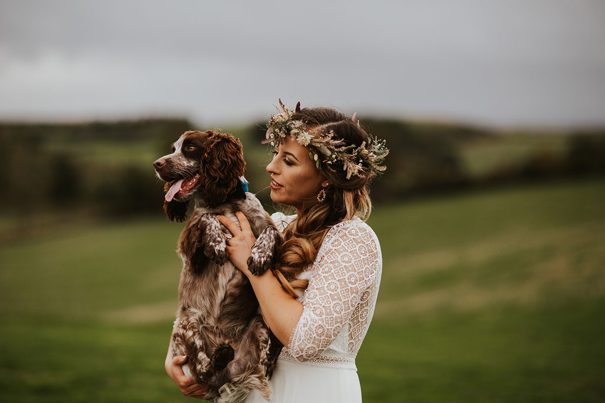 bride-with-floral-crown-carrying-spaniel-dog