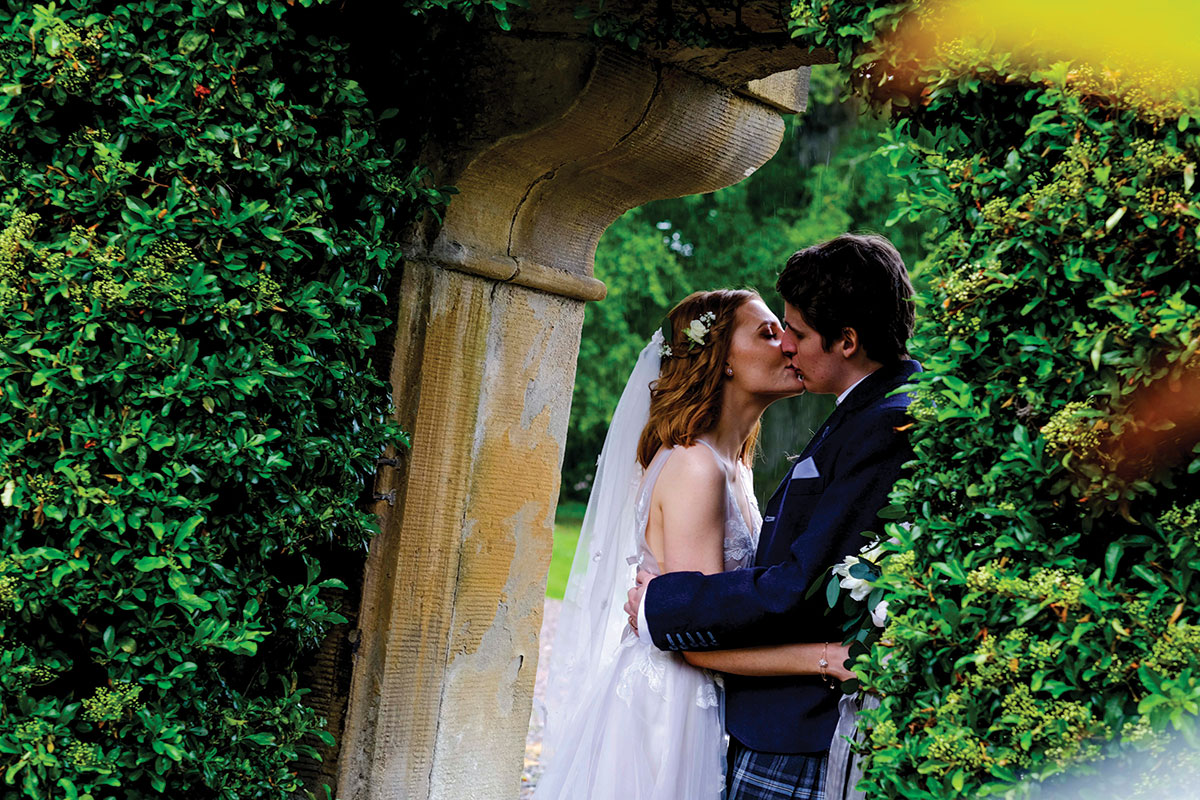 bride-and-groom-kissing-in-archway-on-castle-grounds