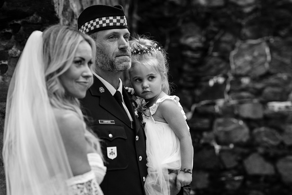 black-and-white-picture-of-couple-and-daughter-during-ceremony