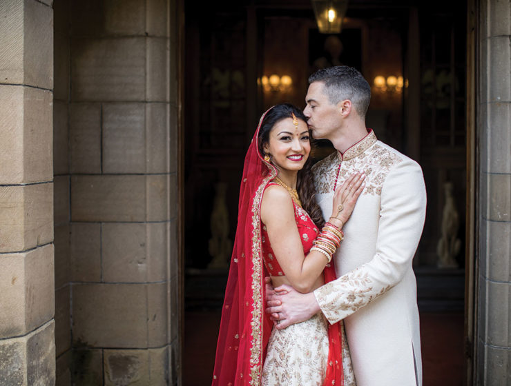 bride-and-groom-in-traditional-dress-in-castle-doorway