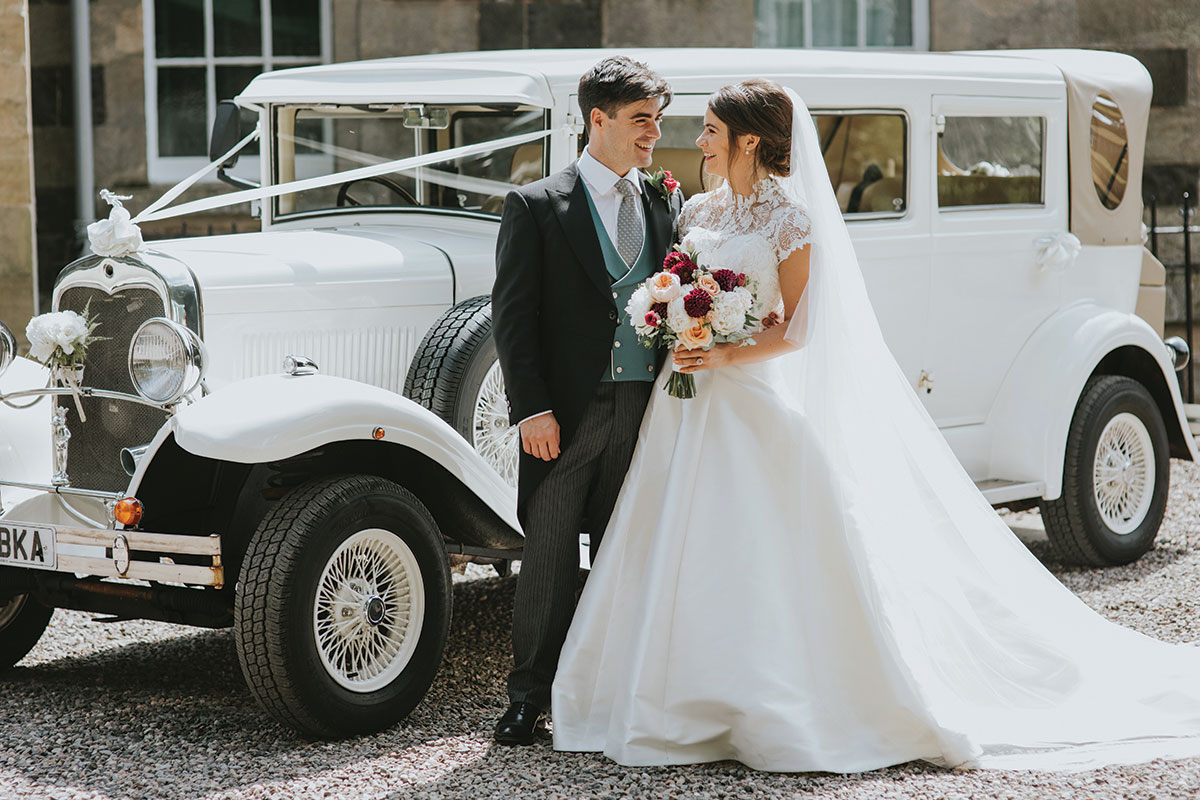 the-couple-standing-outside-a-white-classic-car