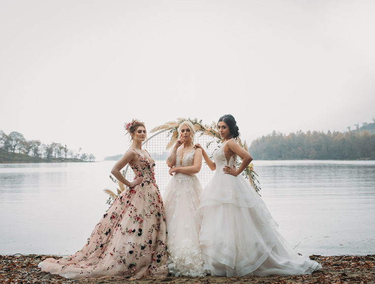 three-brides-in-front-of-water-and-floral-arch