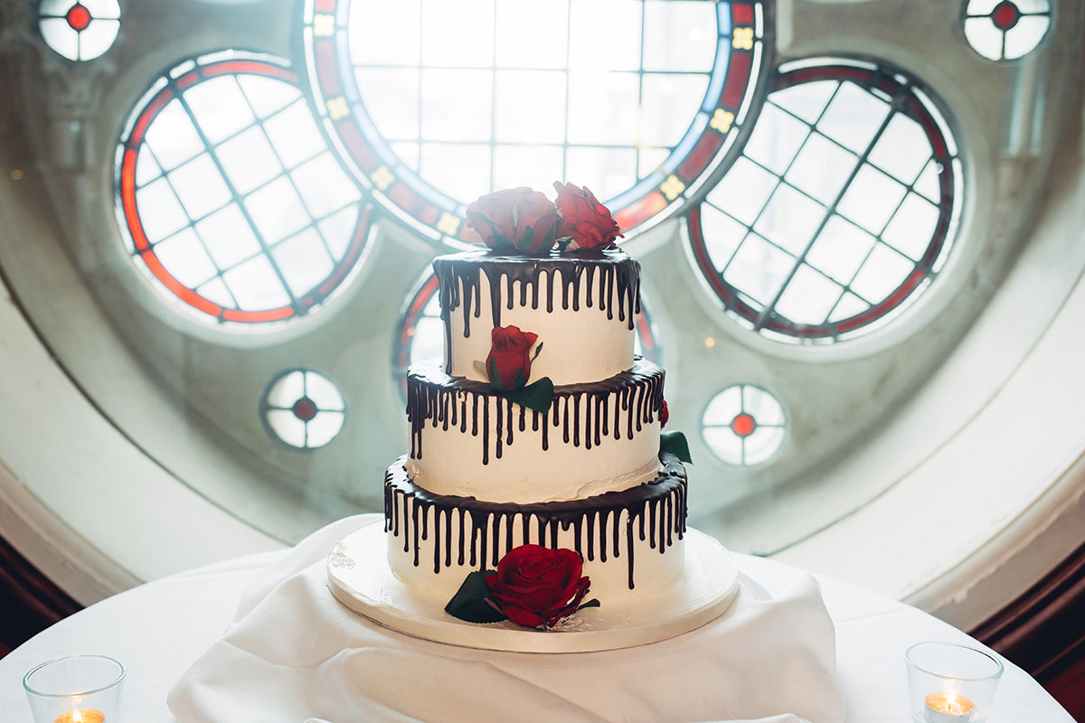 three-tier-wedding-cake-with-chocolate-drips-and-red-roses