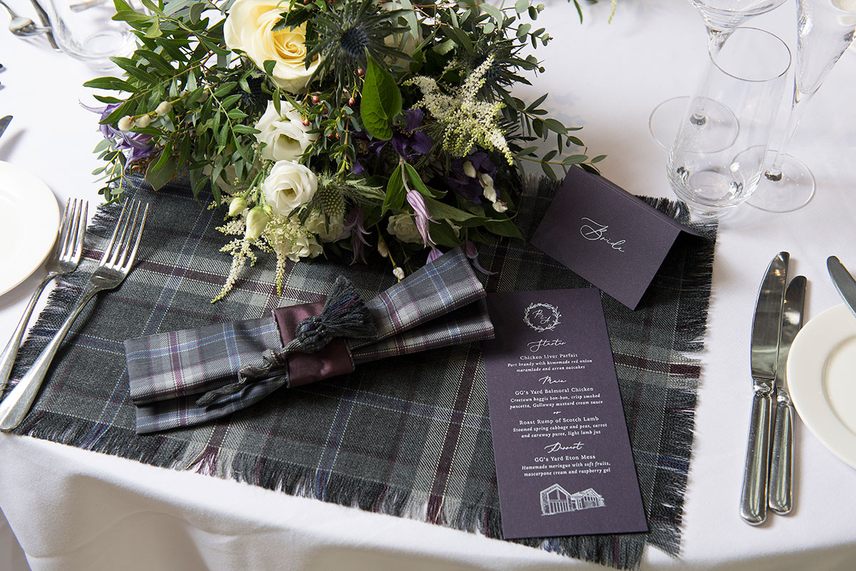 table-setting-with-tartan-and-purple-stationery