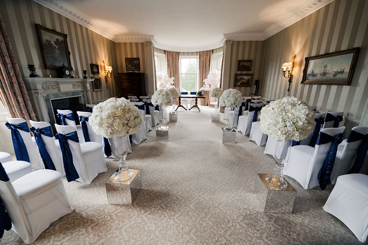 ceremony-room-at-cromlix-with-cherry-blossom-trees-and-chair-covers-with-blue-bows