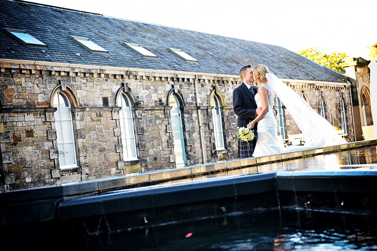 bride and groom kissing next to a water feature