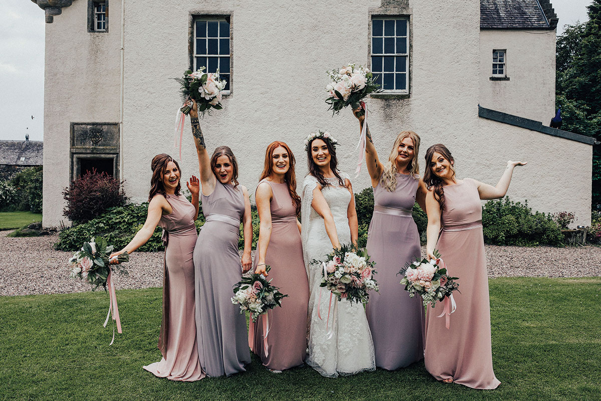 bride-and-bridesmaids-having-fun-in-castle-grounds