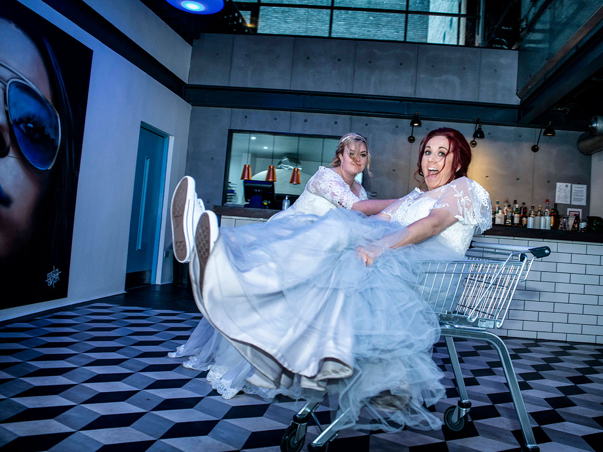 bride-pushing-her-wife-in-a-shopping-trolley-in-arches-cafe-bar