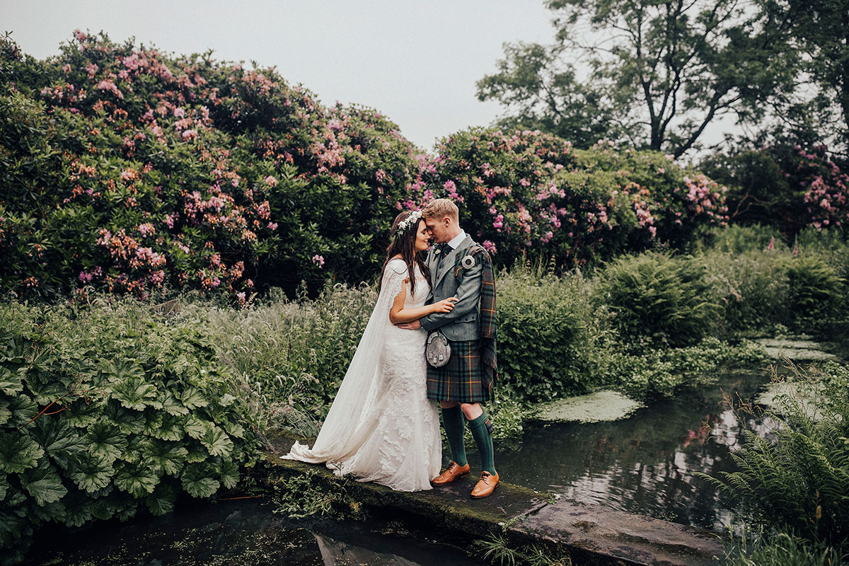 couple-standing-on-a-bridge-over-pond