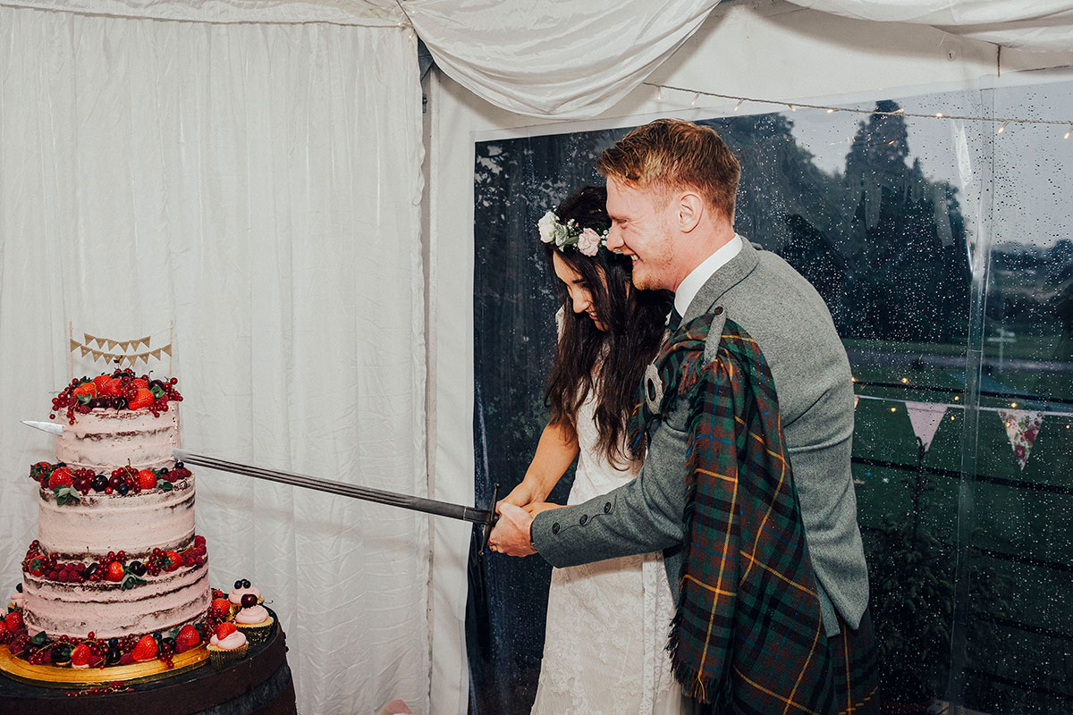 bride-and-groom-cutting-cake-with-a-sword