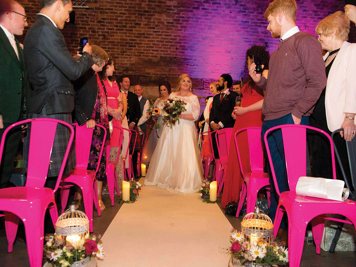 bride-walking-up-the-aisle-with-guests-on-pink-chairs