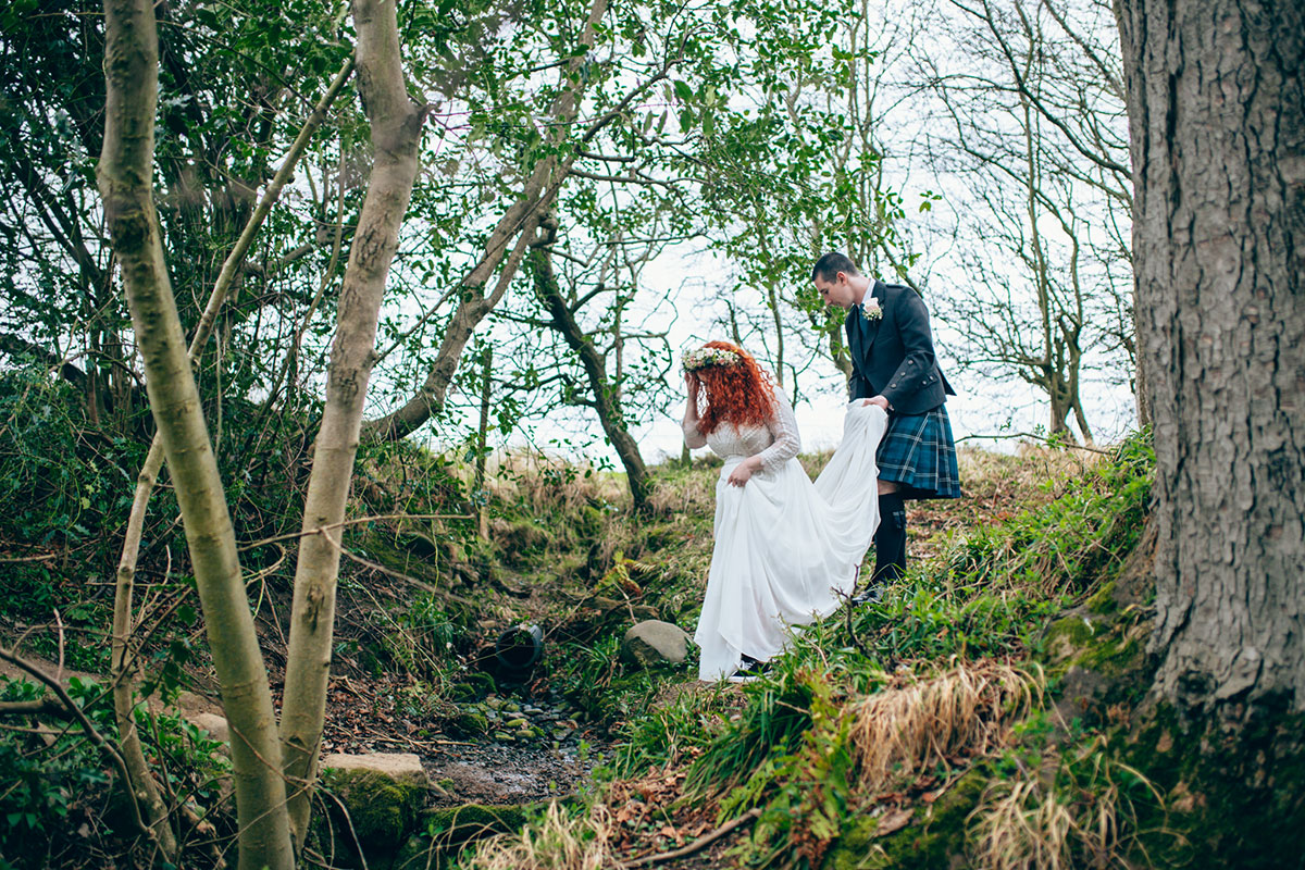 bride-and-groom-walking-down-a-gorge-exploring-the-castle-grounds