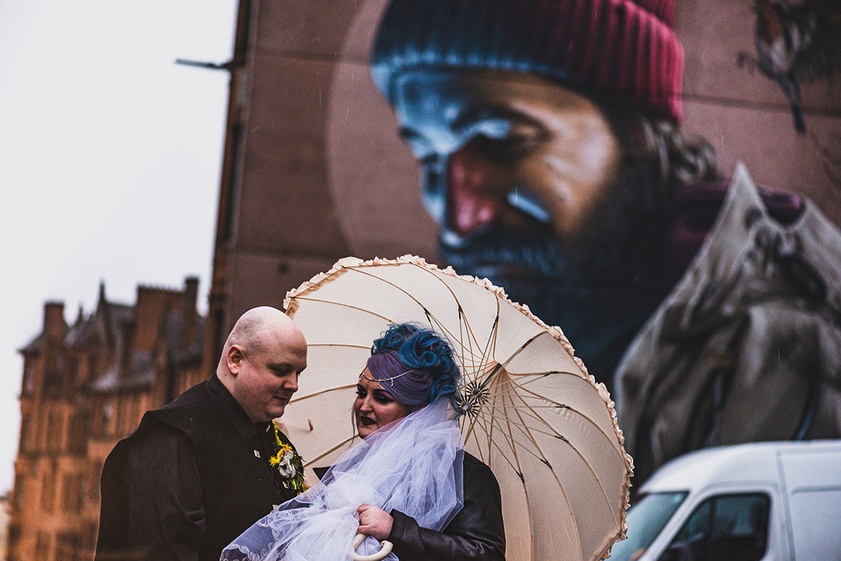 couple-standing-under-street-art-on-side-of-building-in-glasgow