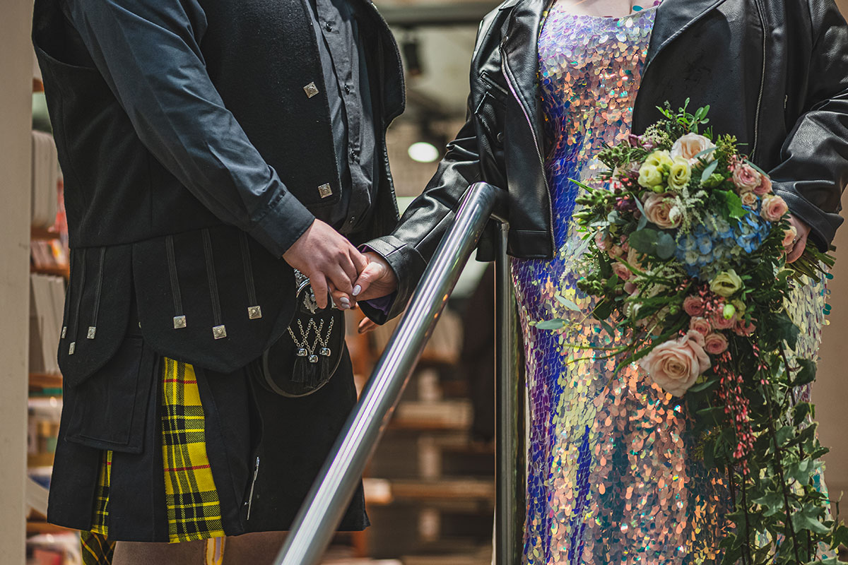 bride-in-sequin-dress-holding-hands-with-groom-in-yellow-tartan-kilt-outfit