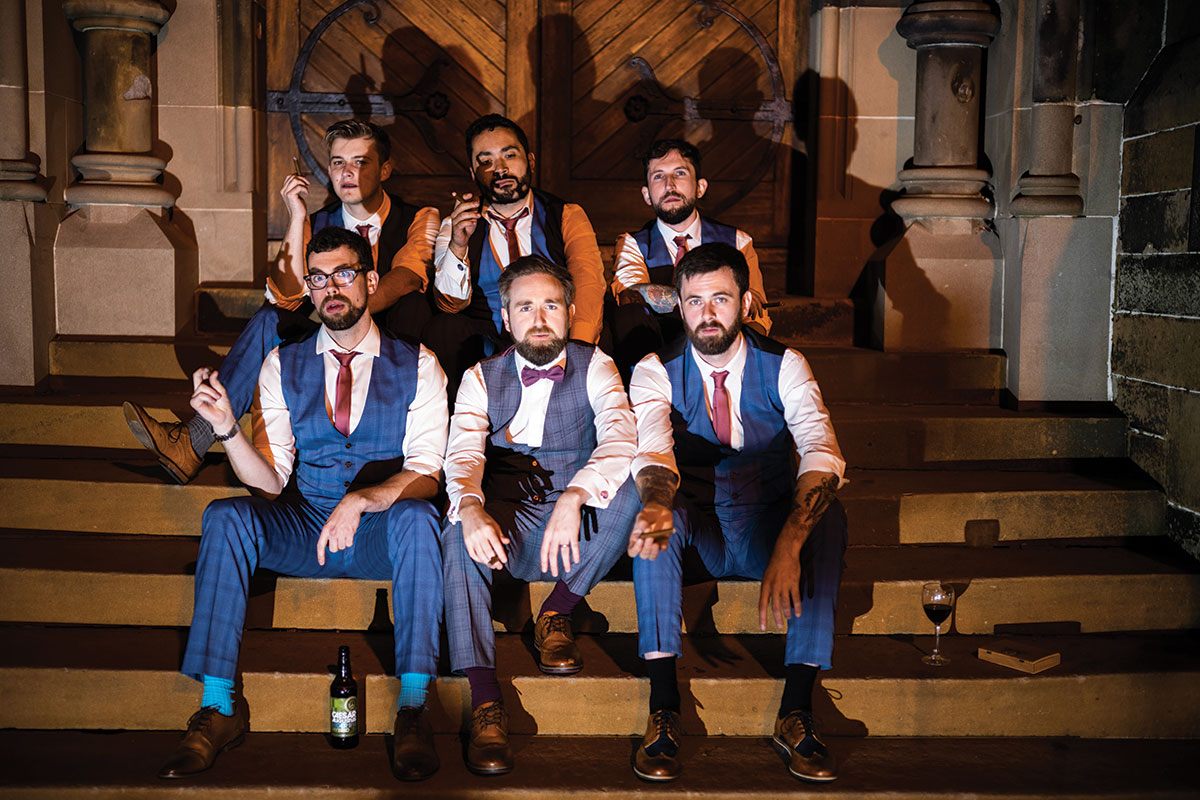 groom-and-groomsmen-sitting-on-steps-outside-at-evening-reception