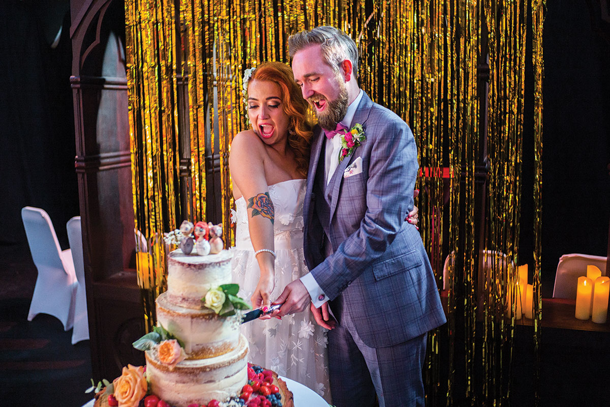 couple-cutting-cake-in-front-of-gold-metallic-curtain