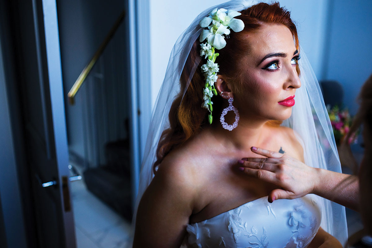 bride-with-red-hair-and-floral-headpiece-having-makeup-done