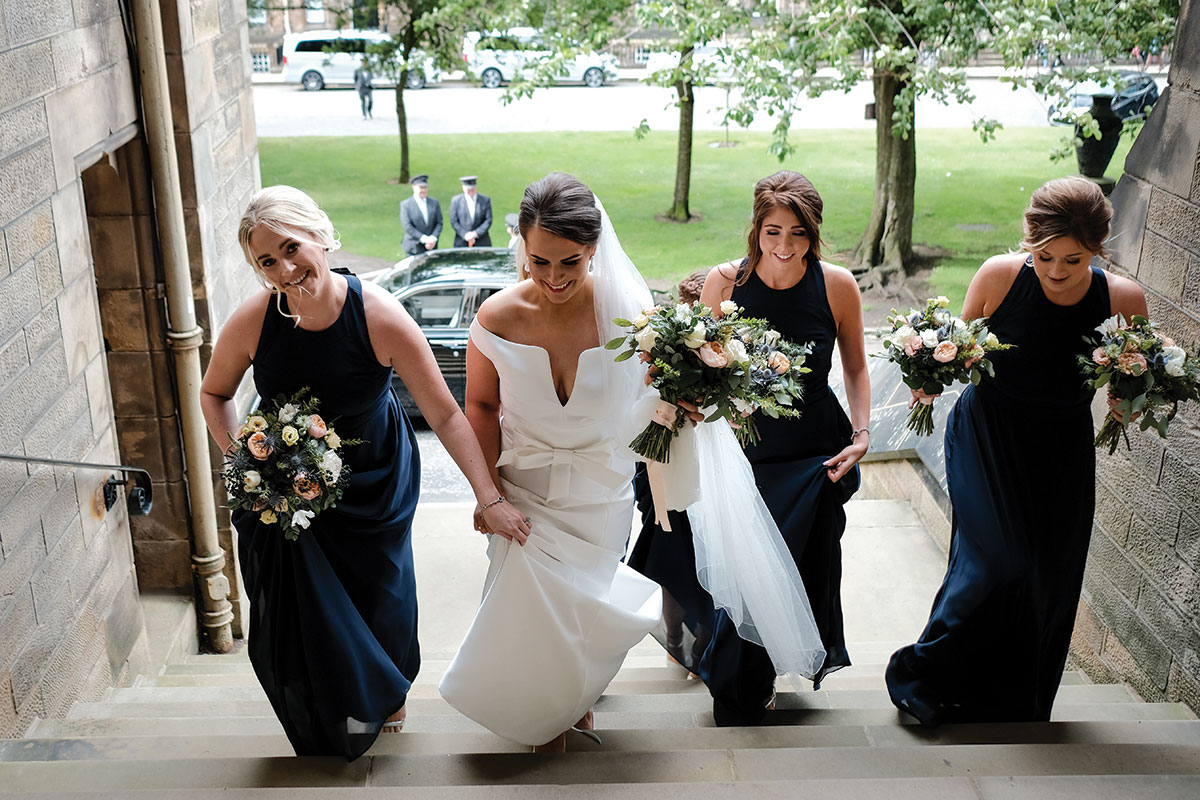 bride-and-bridesmaids-climbing-stairs-arriving-at-glasgow-university