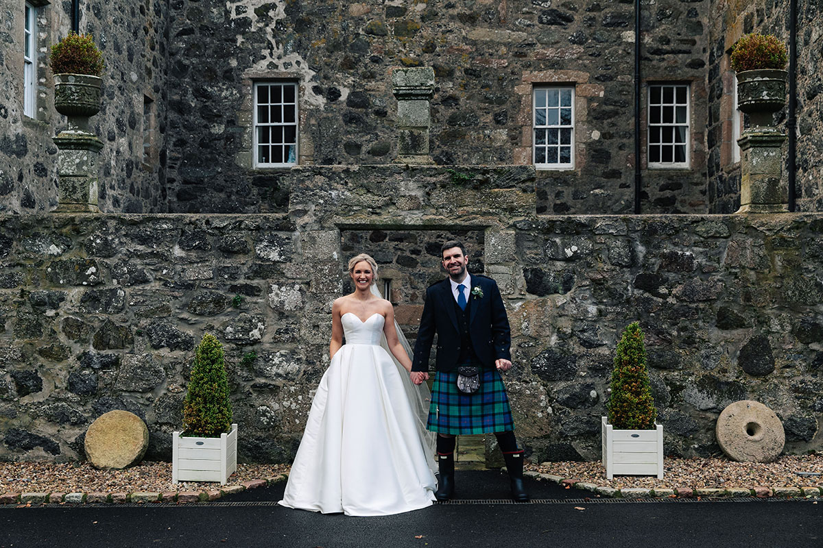 bride-and-groom-outside-barn-at-barra-castle