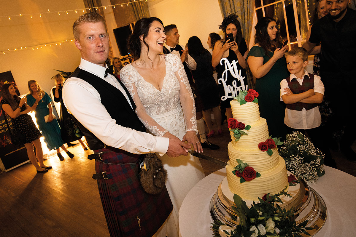 bride-and-groom-cutting-wedding-cake-guests-looking-on