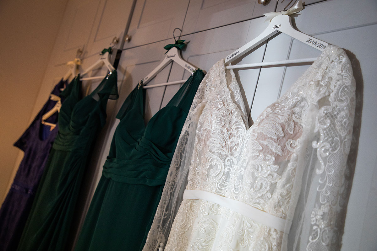 bride-and-bridesmaid-dresses-hanging-up-on-personalised-hangers