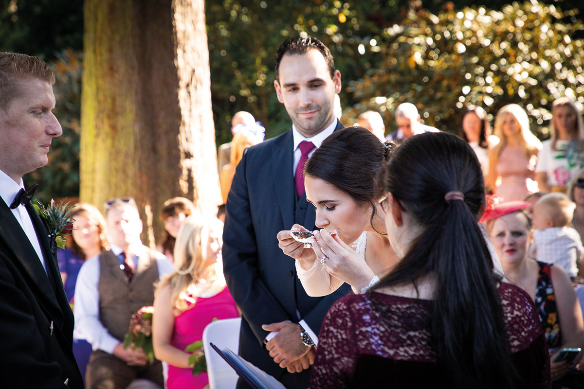 bride-drinking-from-quaich-outside-surrounded-by-guests