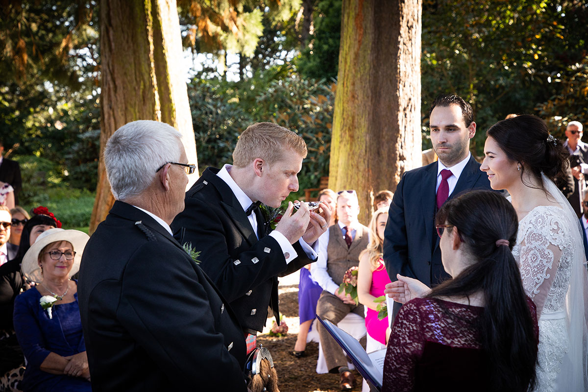 groom-drinking-from-quaich-surrounded-by-guests-outdoors