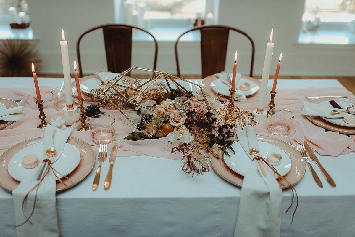 dinner table set with candles, pink table runner and gold terrarium floral arrangement