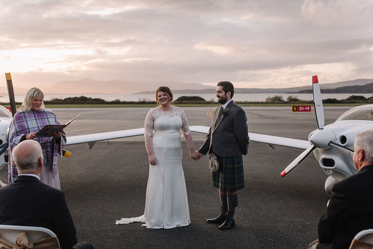 wedding-ceremony-on-runway-oban-airport-with-yellow-plane-landing
