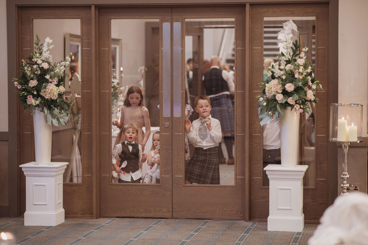 Aboyne Photographics Meldrum House Aberdeen wedding venue children looking through doors