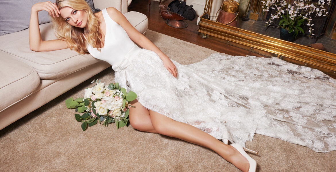 bride leaning on sofa wearing Joyce Young wedding dress