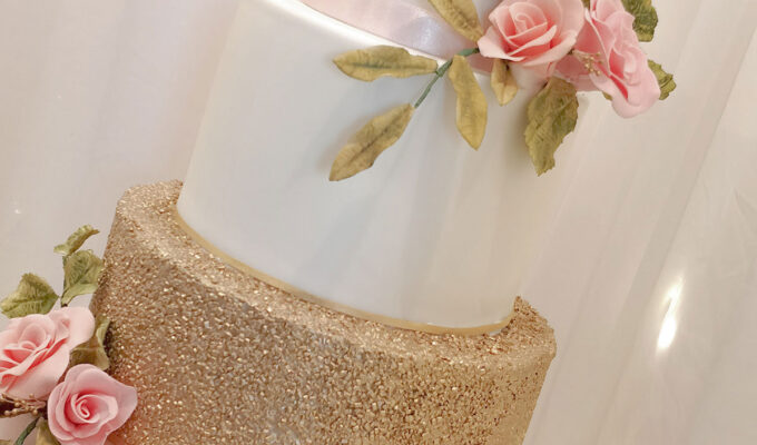 wedding cake with gold glitter and pink roses