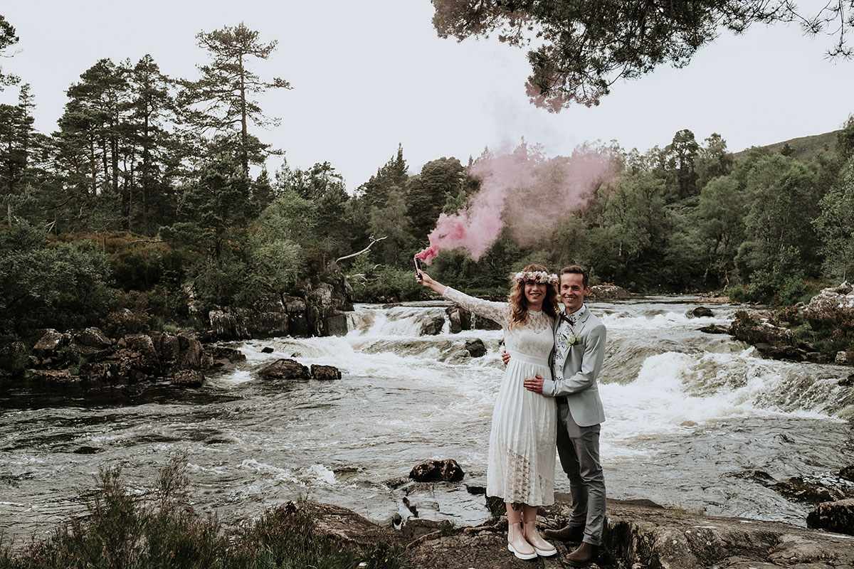smoke bomb elopement bride and groom by river in glen affric