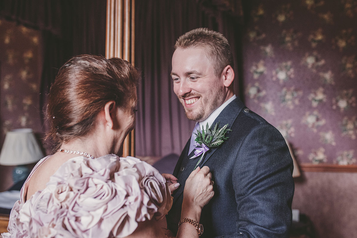 mother of groom pinning buttonhole on groom at Aswanley by Zoe Rae Photography