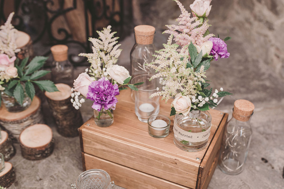 wedding flowers in jam jars and bottles on wooden crate at Aswanley Zoe Rae Photography