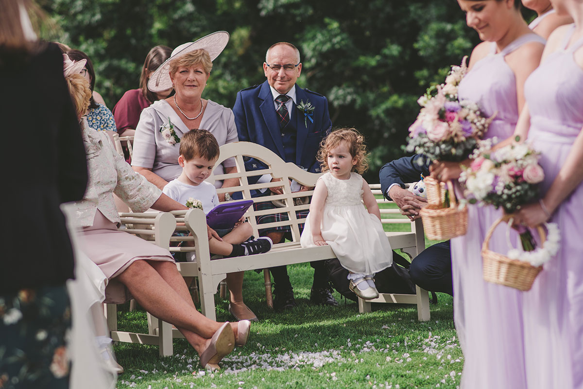 children sitting on bench at outdoor wedding at Aswanley