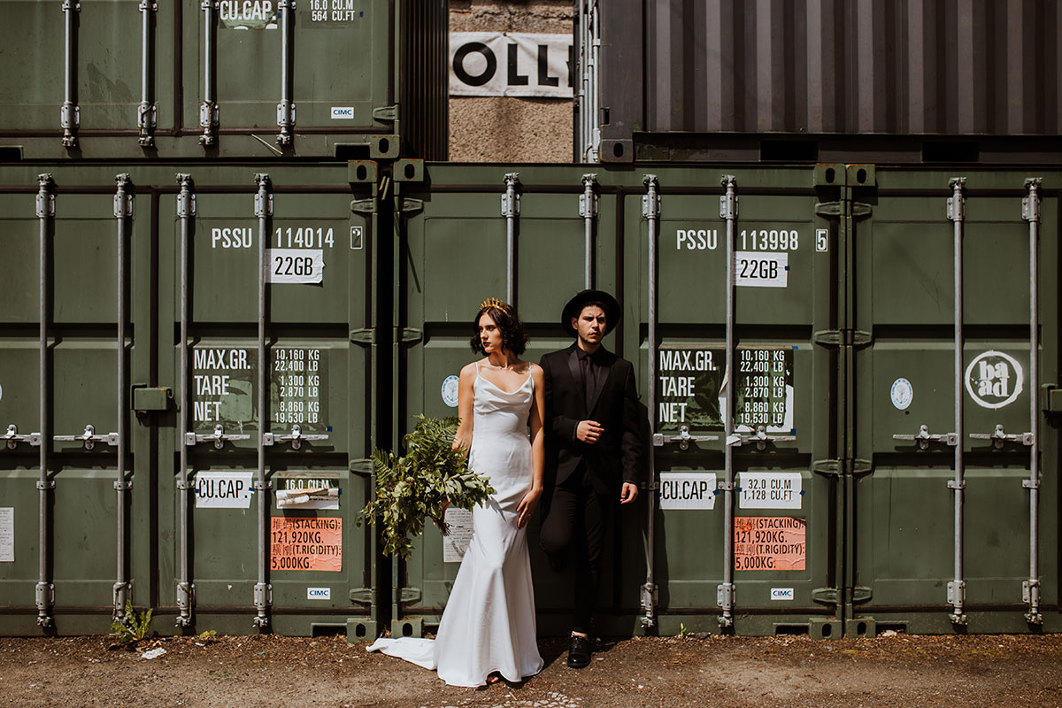 bride and groom beside green container units