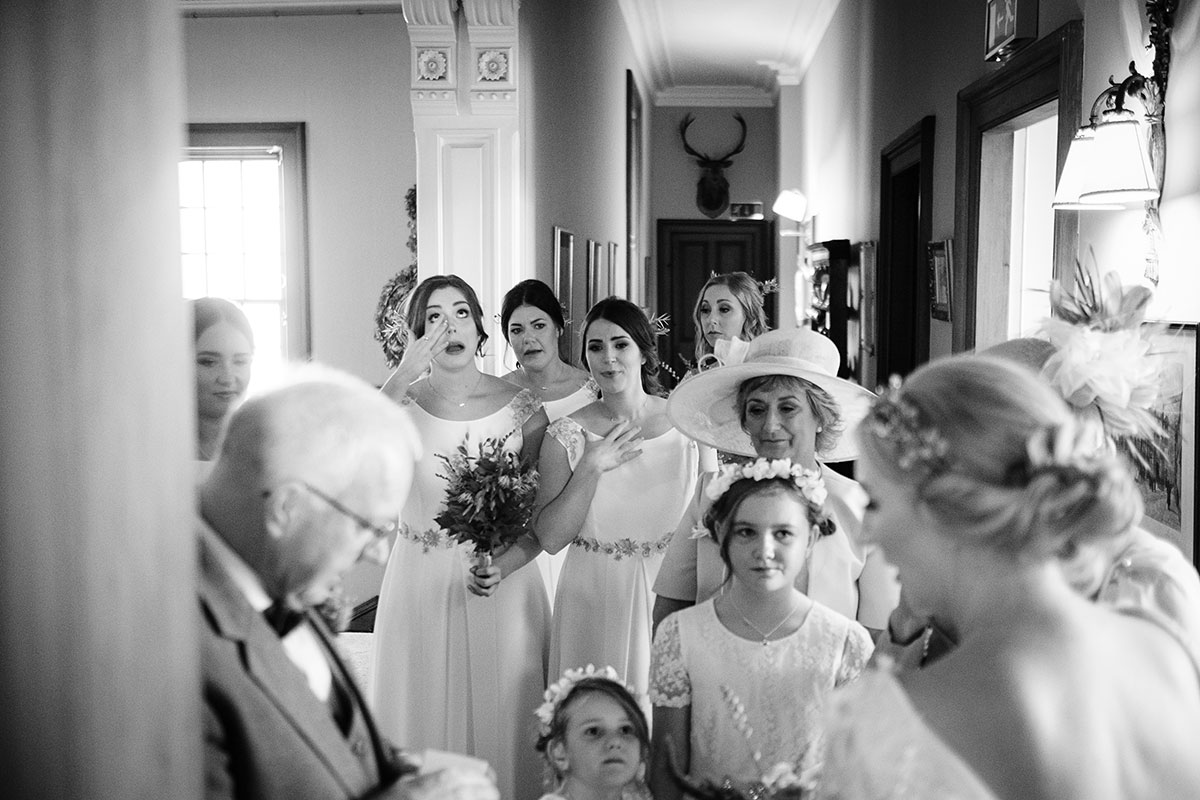 Teary bridesmaids and flower girls seeing bride for first time