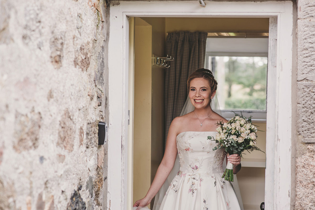 bride leaving house wearing floral wedding dress and carrying bouquet