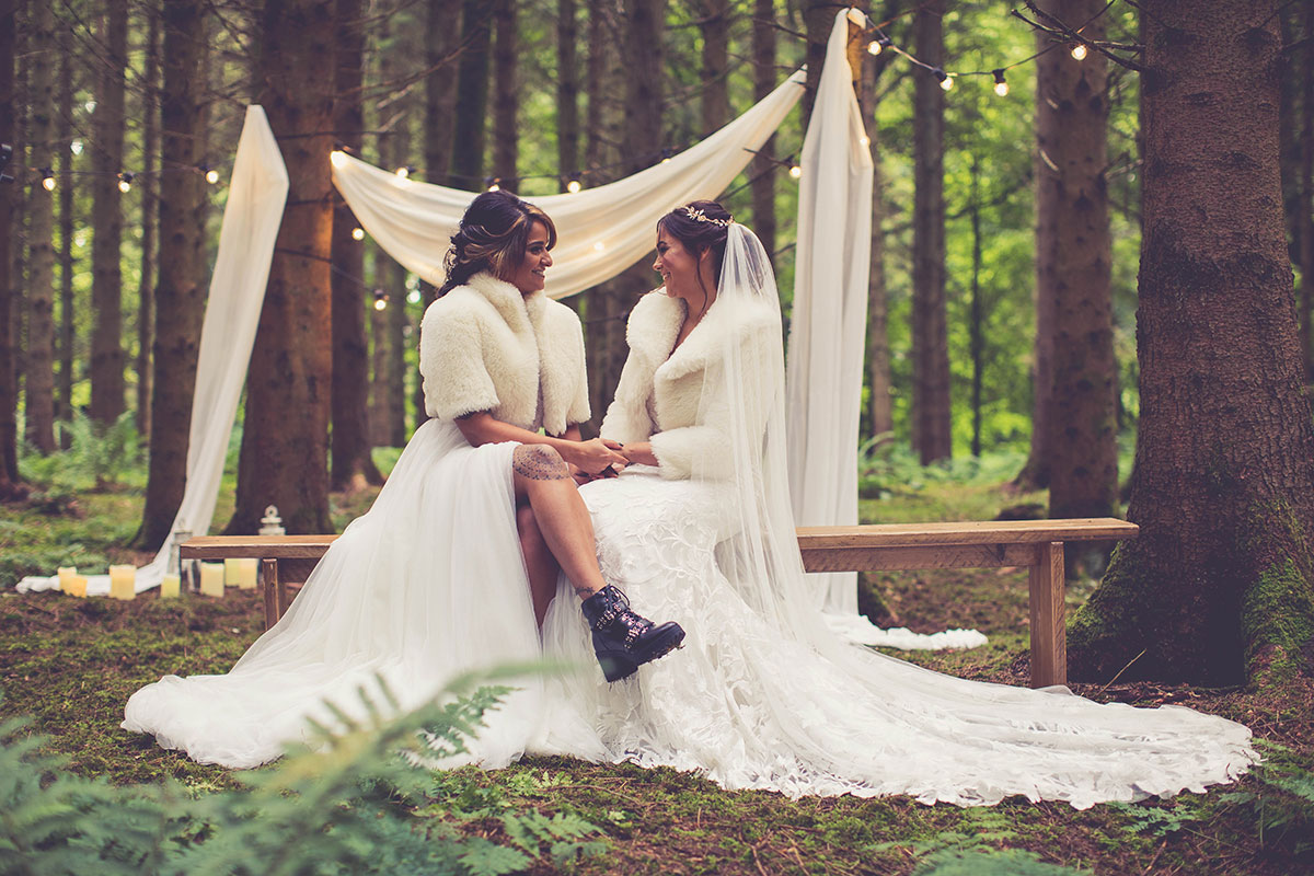 Two brides wearing faux fur jackets by Polly Reid