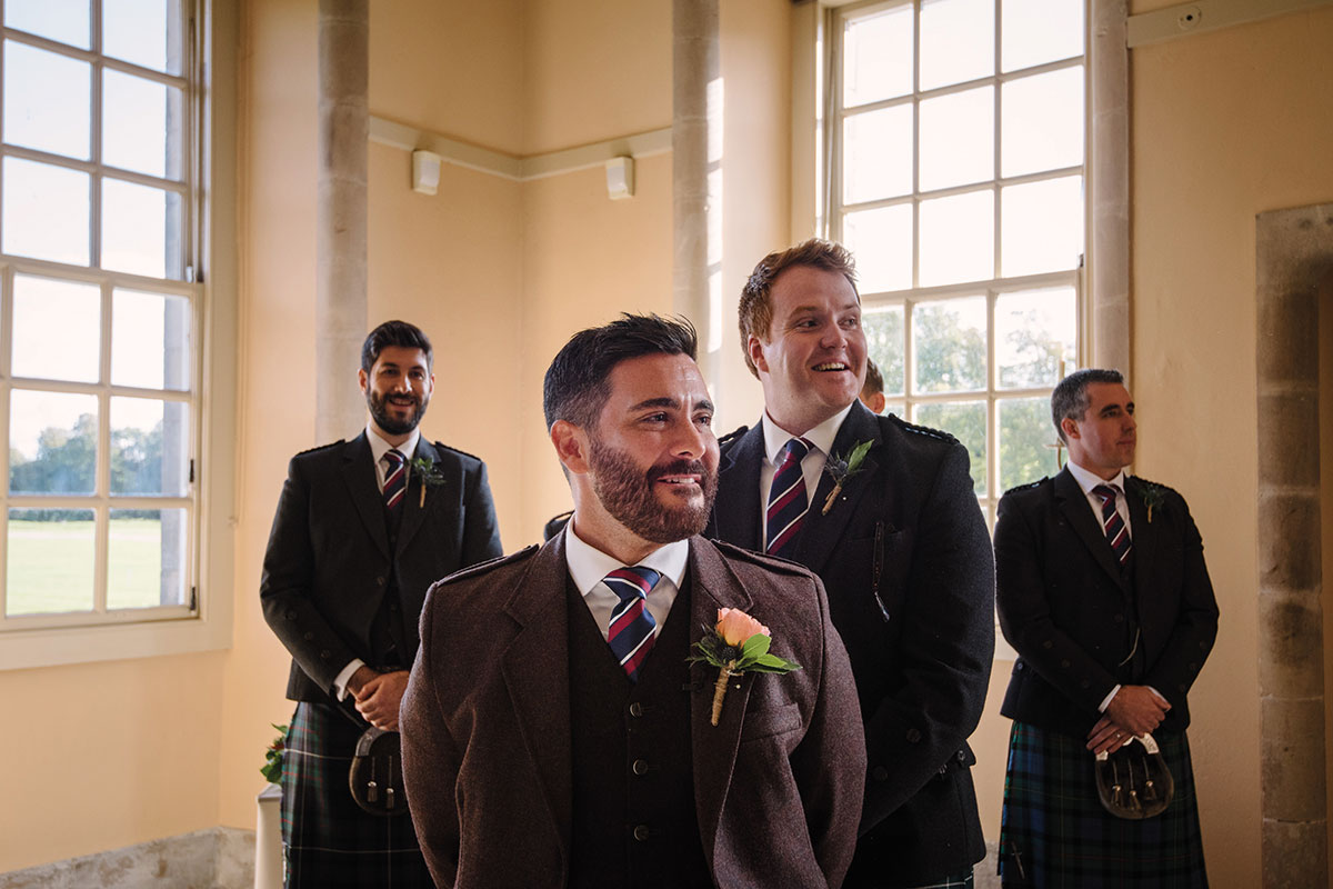 groom looking emotionally at bride as she comes down aisle