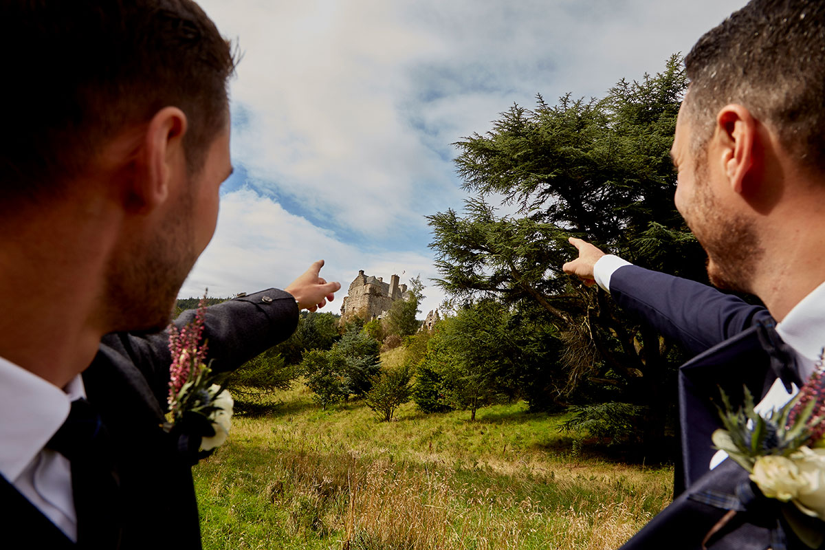 two grooms pointing at Neidpath Castle