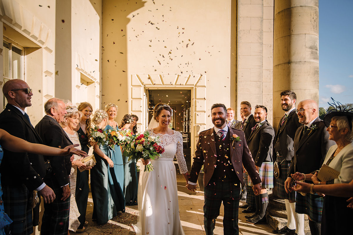 bride and groom showered in confetti outside Hopetoun House