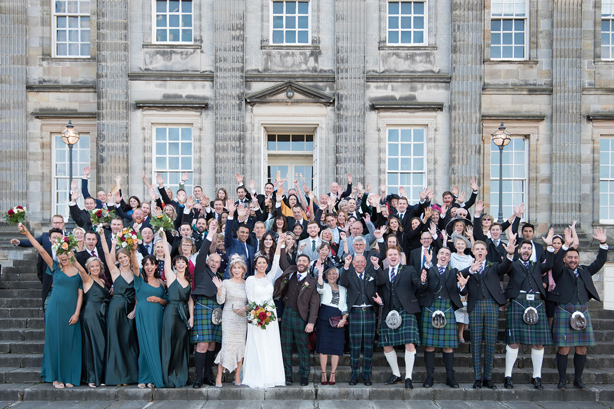 bride and groom with wedding guests outside Hopetoun House