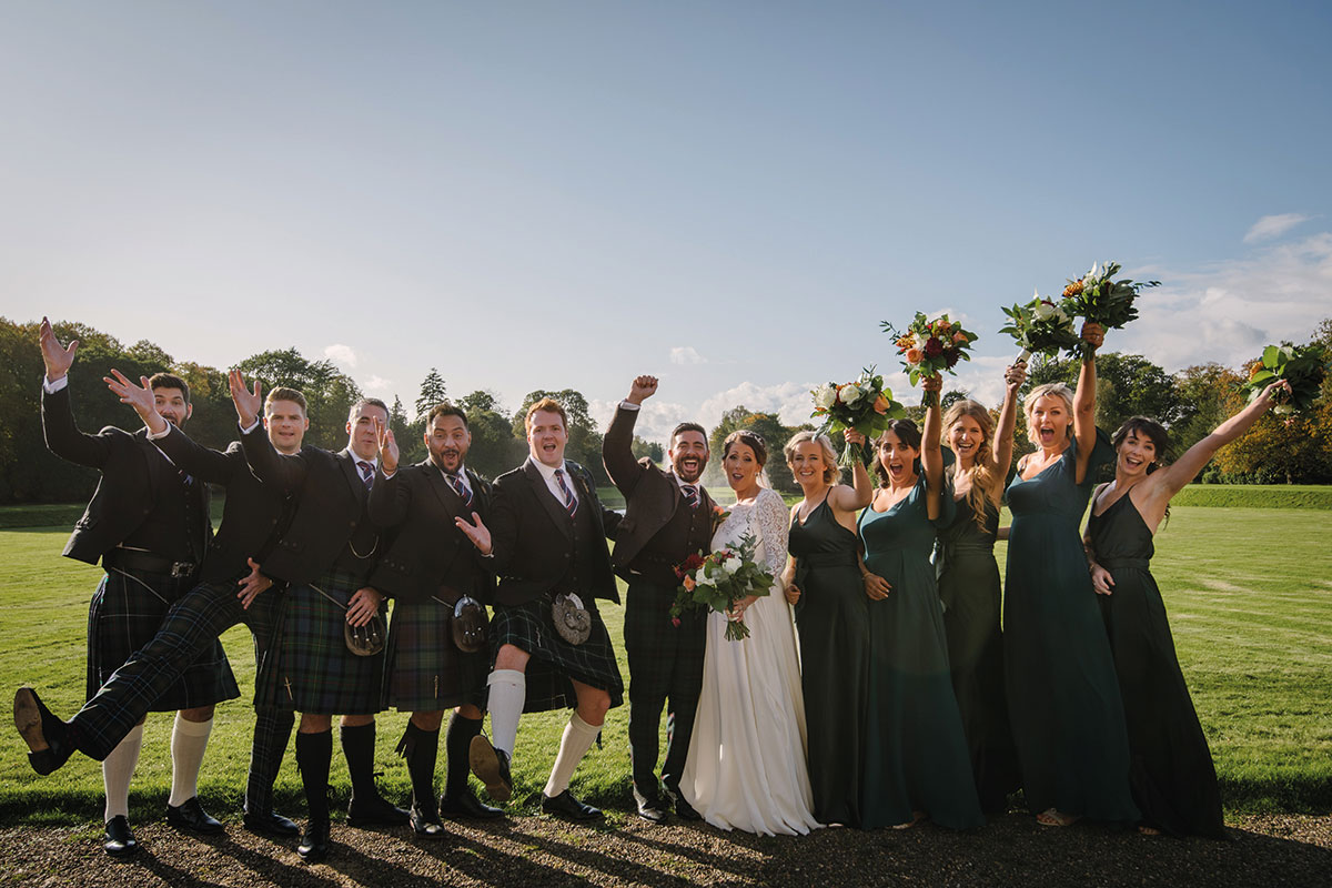 bride and groom with bridesmaids and groomsmen with hands in the air